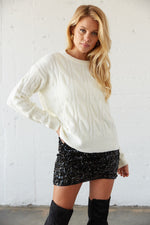 White soft knit sweater with cable knit design.