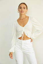 White long sleeve top with cinched front.