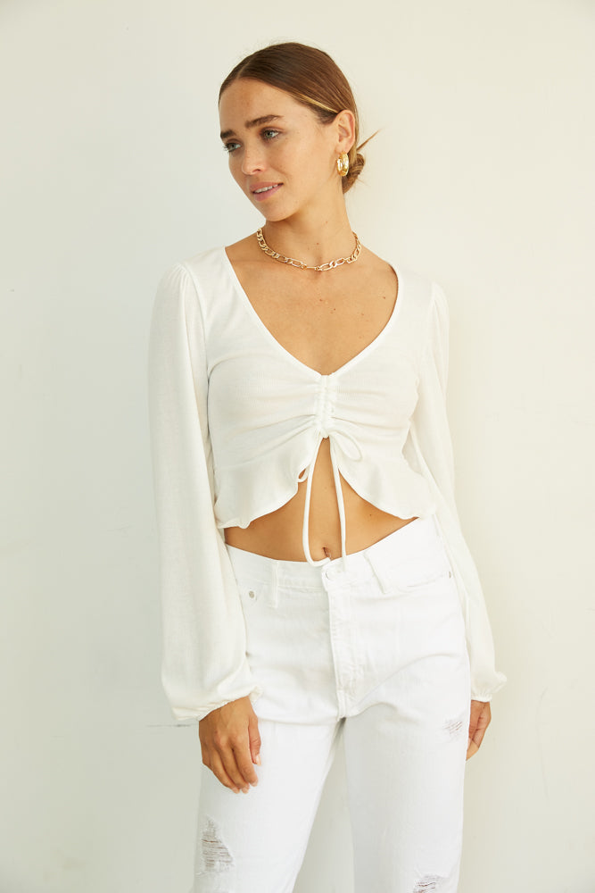 White long sleeve top with ruffle trim.