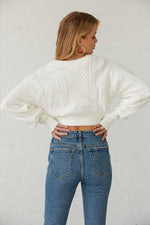The back of this sweater has a cable knit design and a ribbed hem.