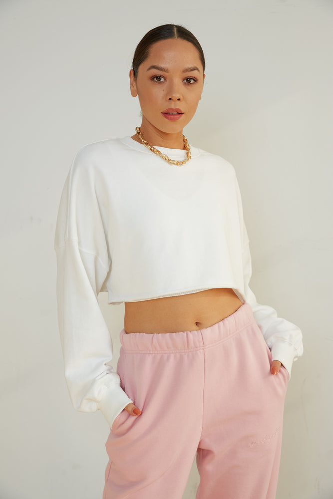 White cropped sweater with raw hem.