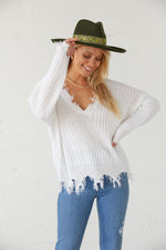 Cute white knit sweater with raw distressed hem.