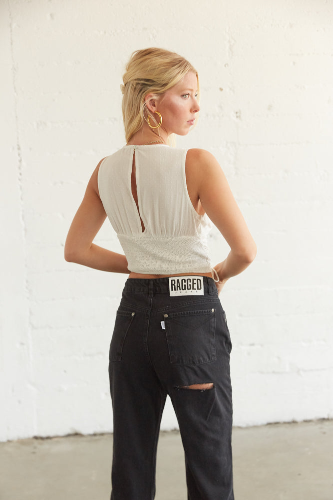 The back of this top has smocked detailing and a cut out with a button closure.
