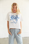 White boxy t-shirt with blue graphic on it.