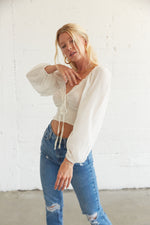 This white crop top has long sleeves and a smocked body.