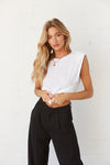 White muscle tee with black pants.
