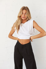 White muscle tee with black trousers.