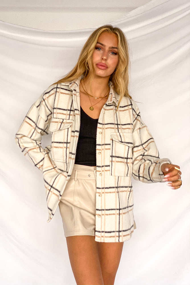 This oversized flannel has a button up front and a neutral plaid print.