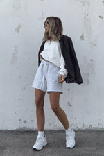 High rise bermuda sweat shorts with white sweatshirt.