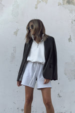 Sweat shorts with leather blazer and white sweatshirt.