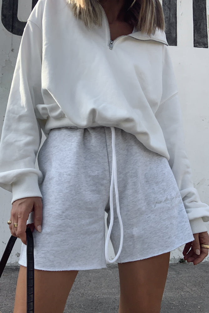 White pullover sweatshirt with zipper front.
