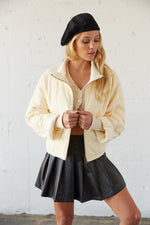 Cream quilted bomber jacket with leather skirt.