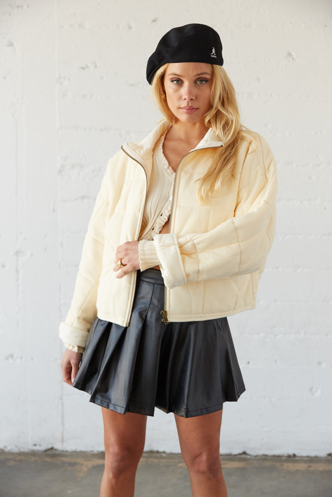 Cream quilted bomber jacket with zip up front and stand up collar.