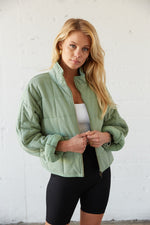 Green quilted bomber jacket with the sleeves rolled up.