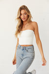 White ribbed knit tube top with puddle jeans.
