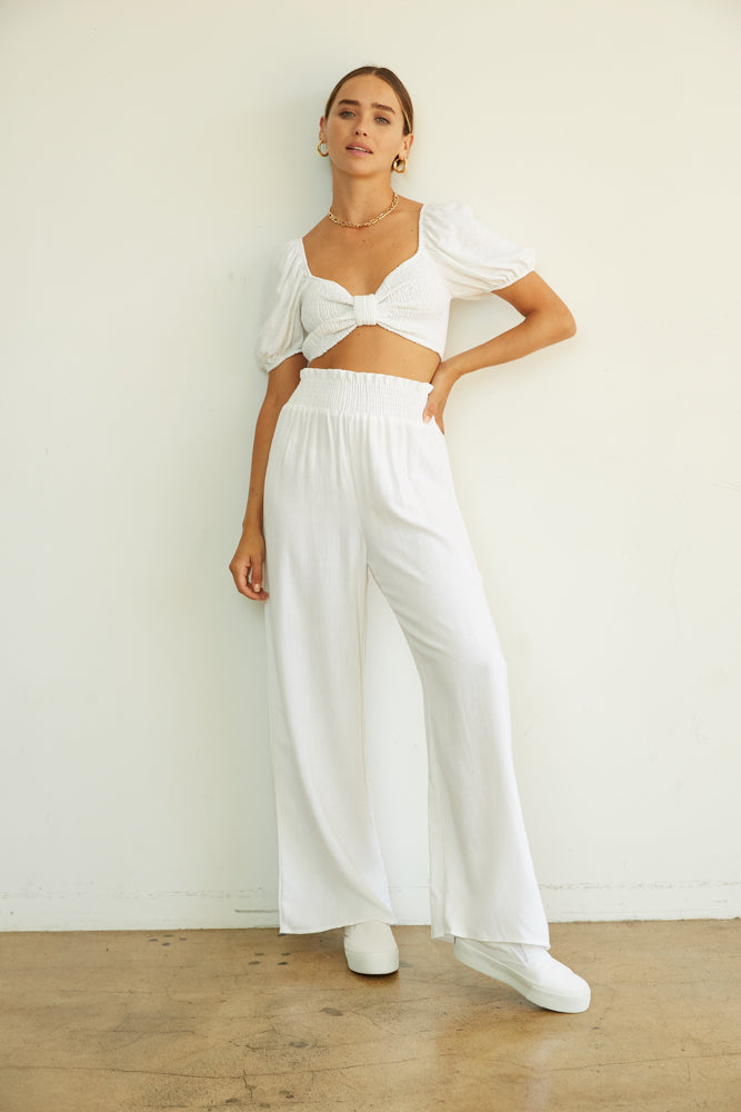 White wide leg pants with smocked crop top.