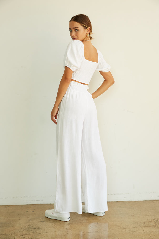 White linen pants with smocked elastic waist.