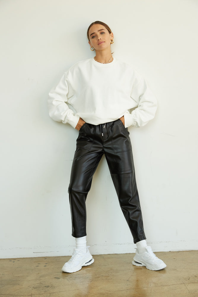 Black vegan leather pants with white sweatshirt.
