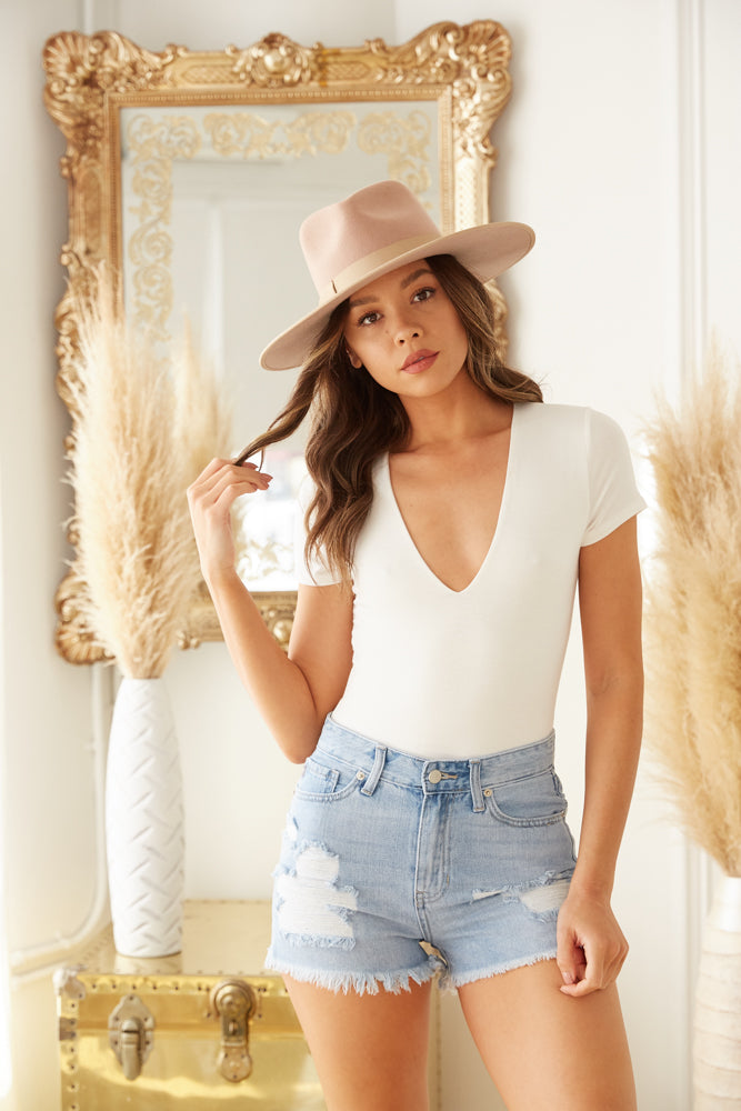 White v neck bodysuit with distressed denim shorts.