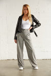 Grey pleated trousers with wide leg design.