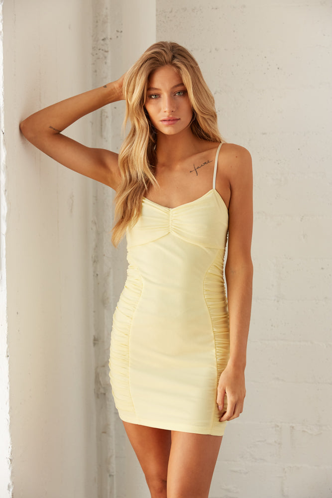 Yellow mesh mini dress with ruched detailing.