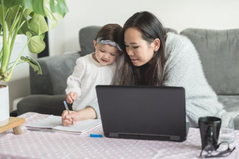 Woman writing on a piece of paper with her daughter next to her