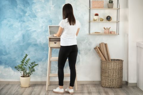 Woman using standing desk at home.