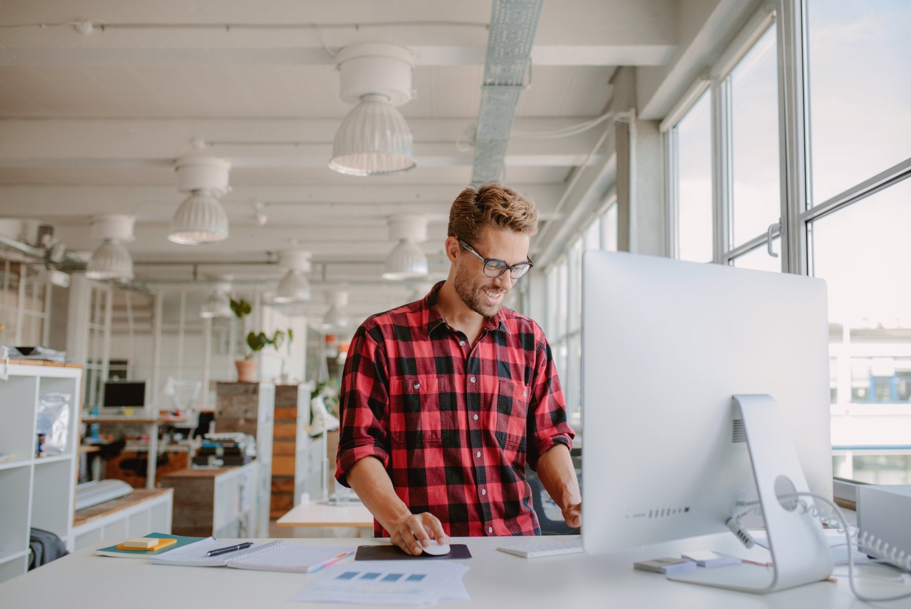 Man standing at his desk working