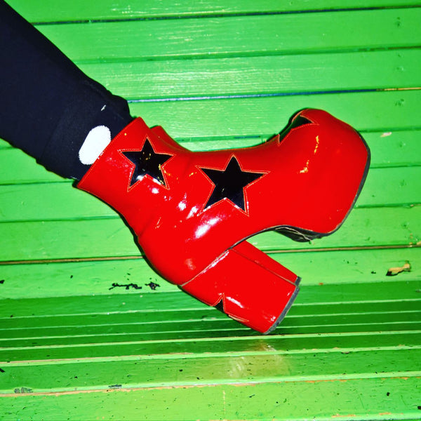 Red Patent Leather Platform Circus 70's Boots with Black Stars Modelled on a Green Bench