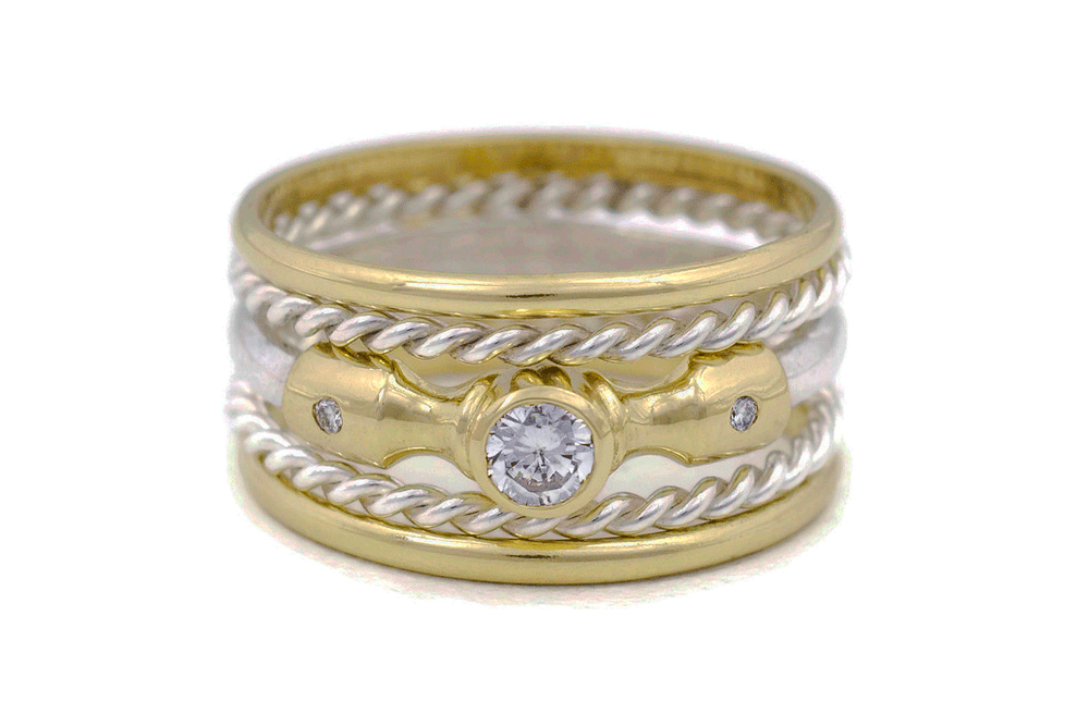 Lighthouse 5 Ring Stacked Set featuring Lighthouse Ring featuring a large ethical lab-grown diamond in the center, offset by 2 smaller ethical diamonds, in an 18K fairmined gold setting. This ring has 2 fairmined silver rope twist rings either side, and 2 x 18K fairmined gold thin plain bands on top and bottom.