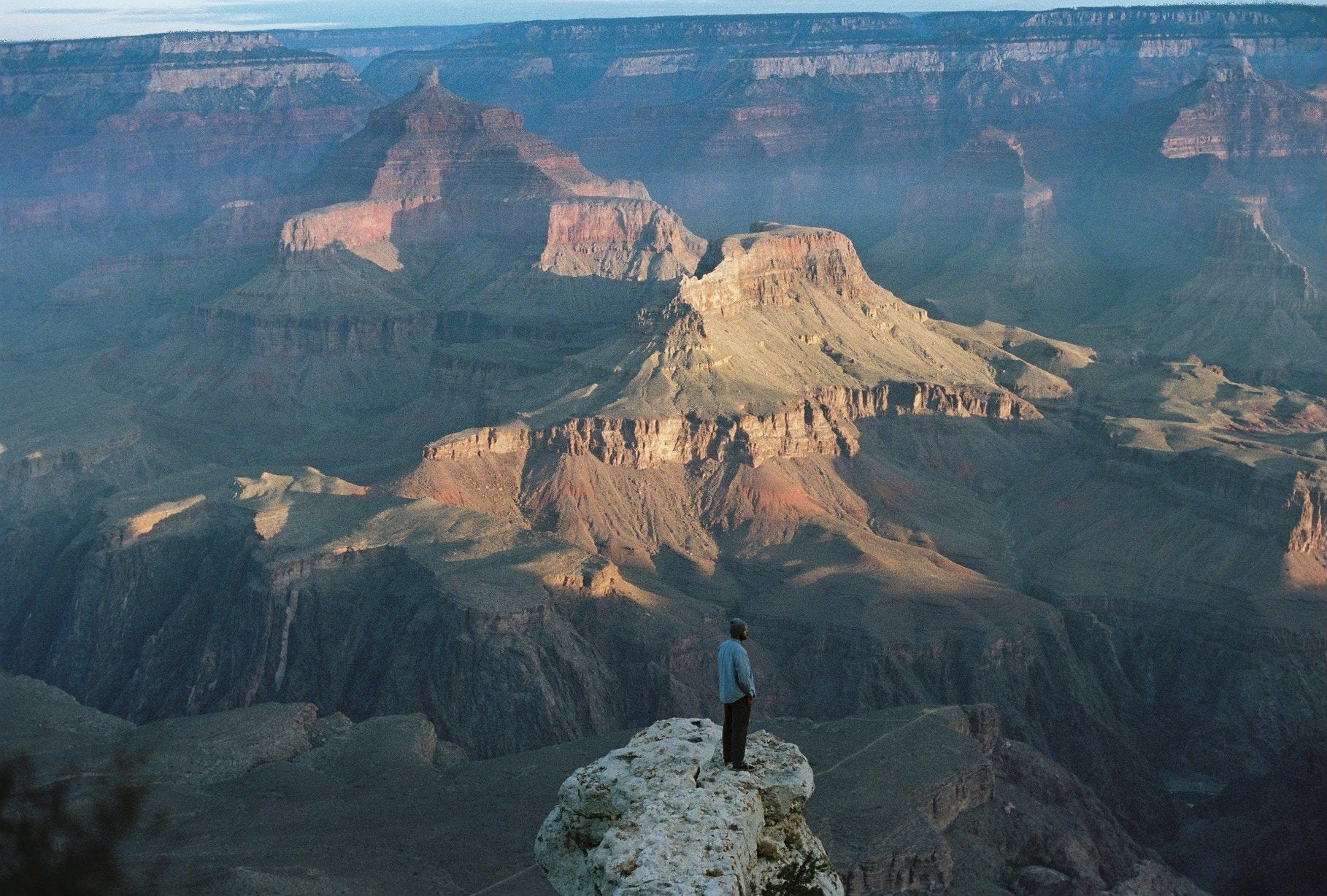 Danny standing on sketchy bute in the grand canyon at sunrise