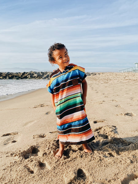 Toddler wearing sustainable swim poncho at the beach