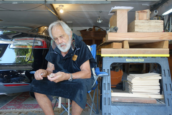 Tommy Chong hanging out in a car garage while wearing a sustainable changing poncho