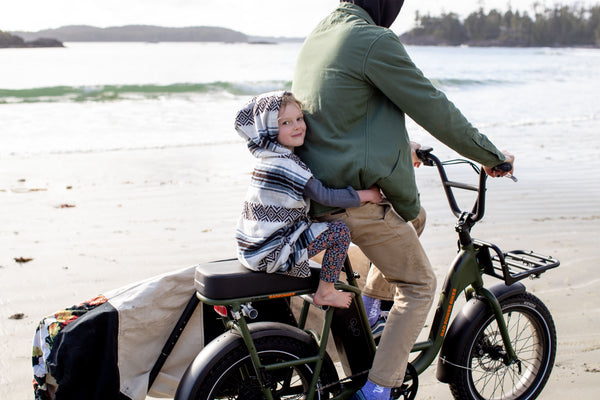 Father Daughter bike ride along the beach in sustainable surf poncho