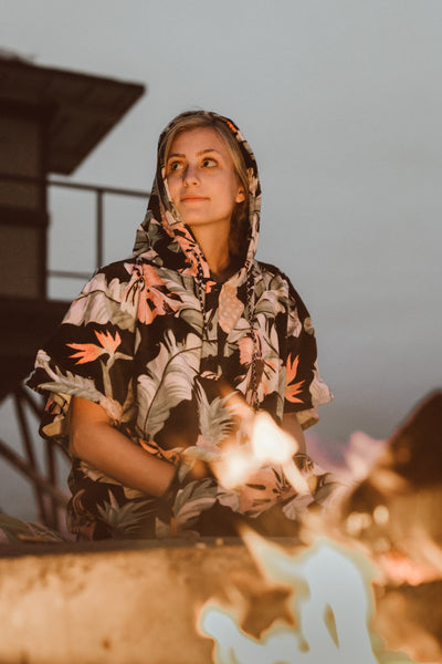 Women in sustainable poncho at bonfire located in Southern California