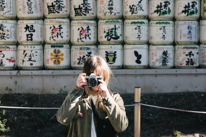 Temple in Tokyo with barrels of Sake that have traditional art and kanji on them