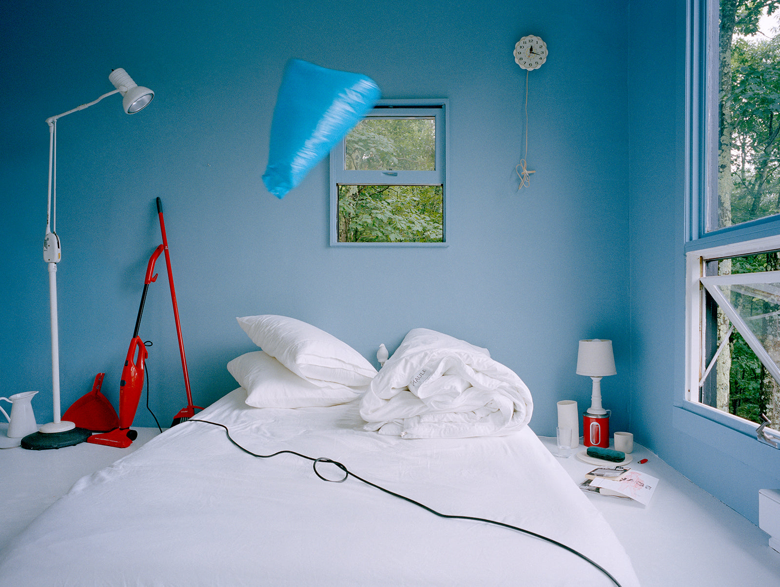 weird bedroom scene with vacuum cord across white bedding and blue bag flying through the air