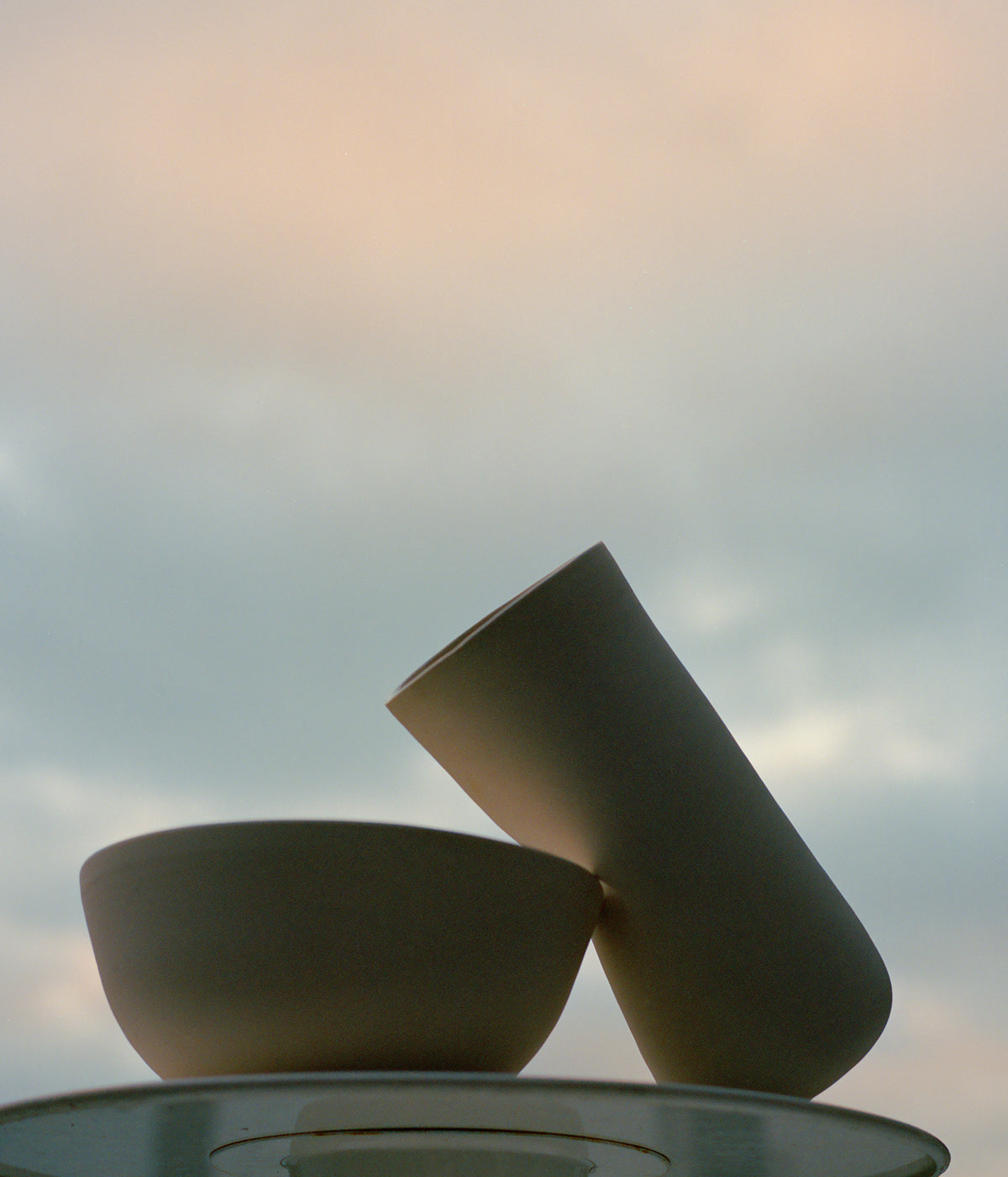 white porcelain hand-thrown ceramics on table against summer evening sky with soft clouds and orange sunset