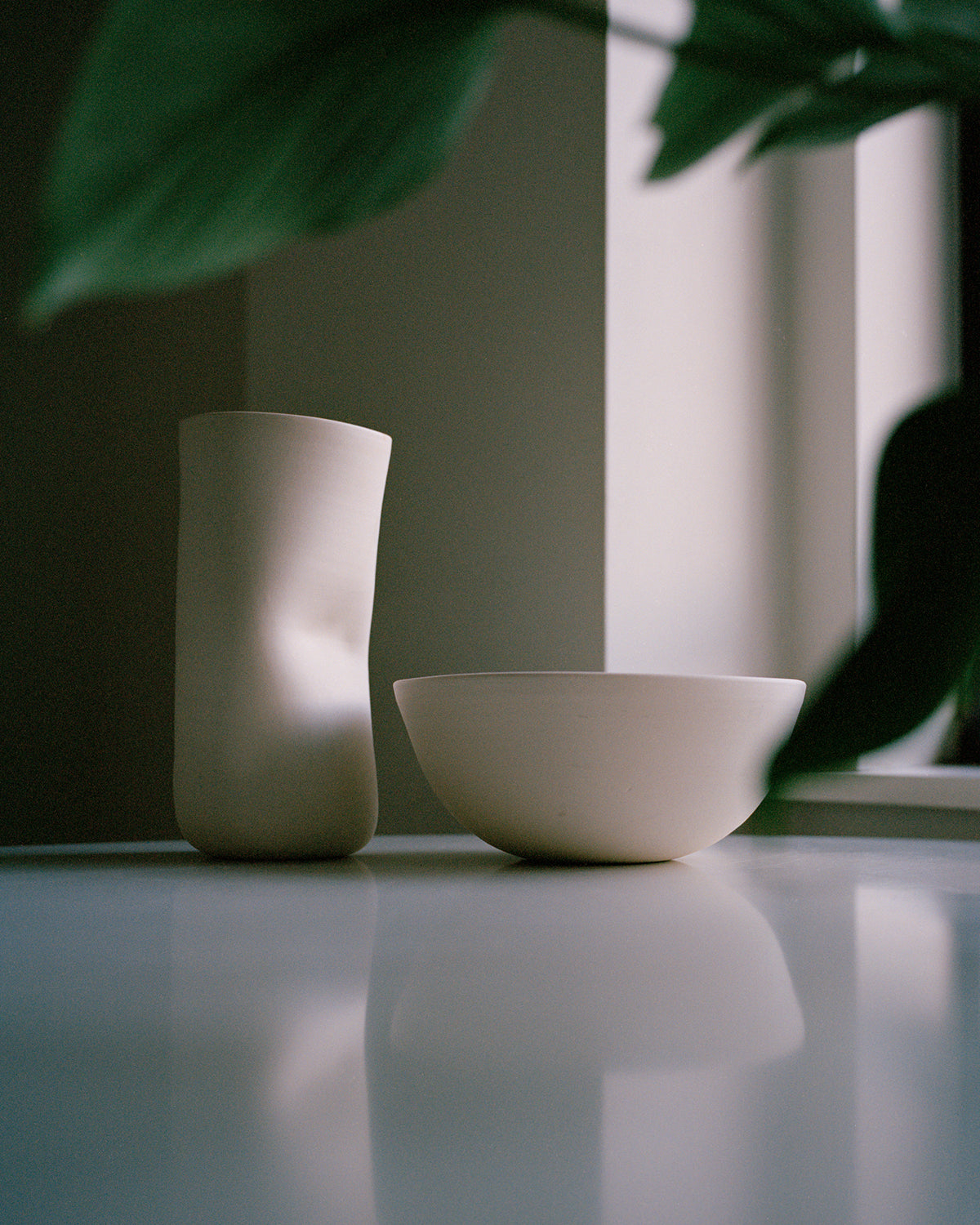 two designer ceramic homewares on table with house plants