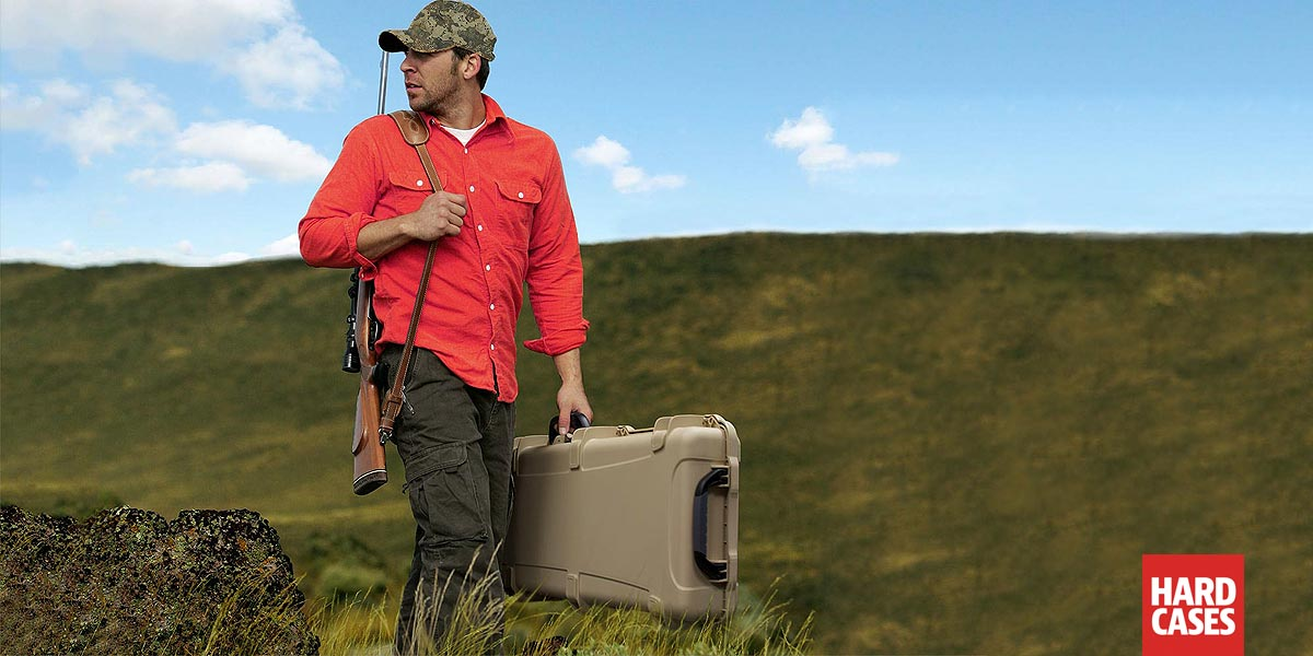 Hunter walking with rifle and Nanuk Hard Case 990