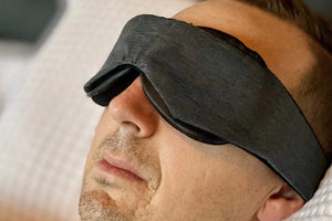 Man Wearing light blocking Sleep Mask