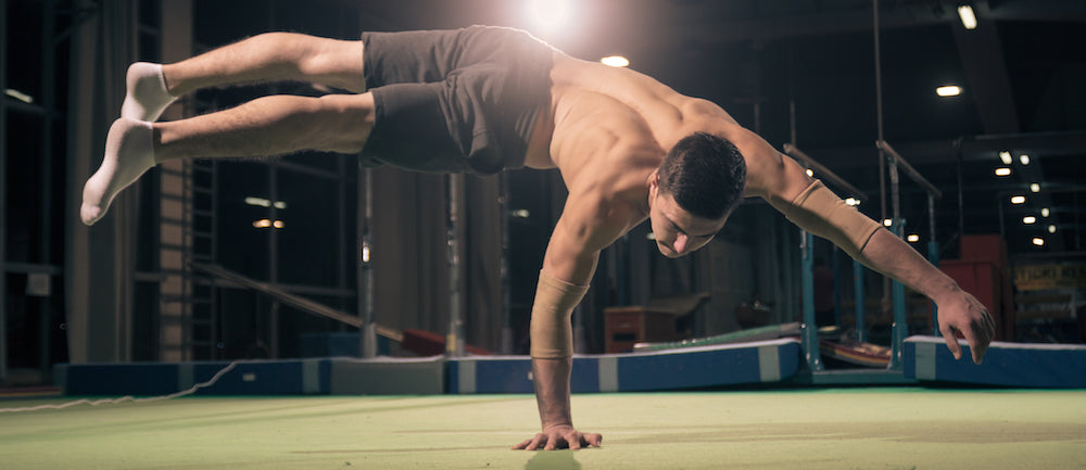 Man doing one armed handstand plank
