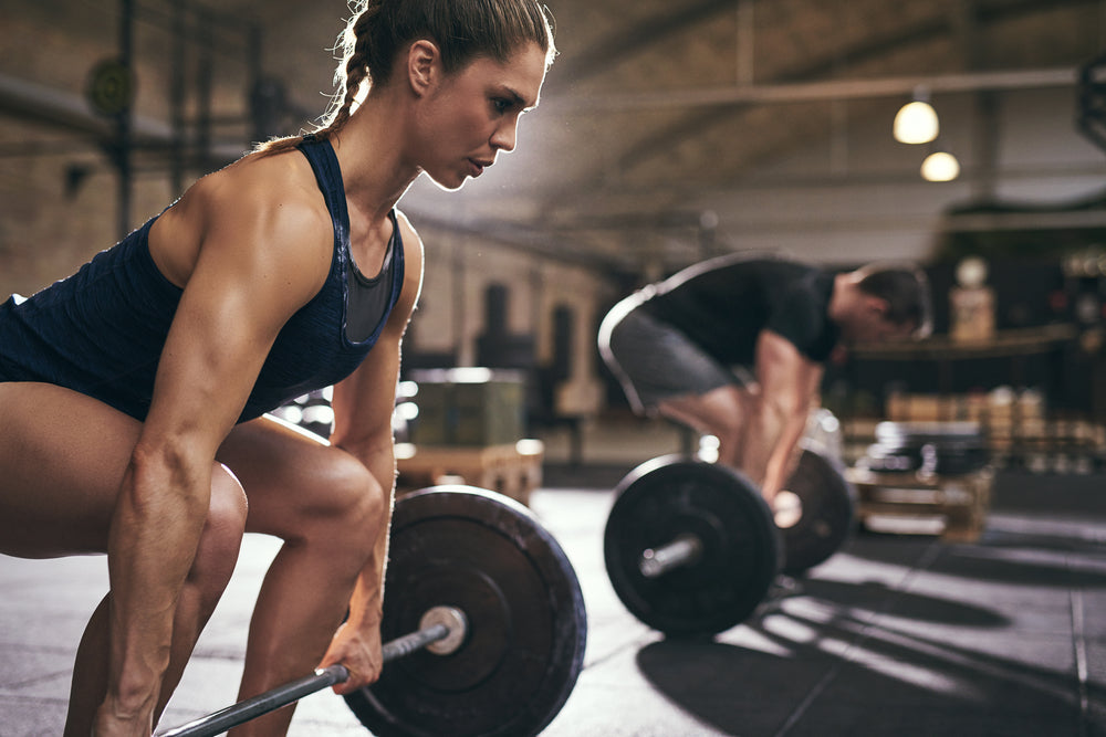 Woman and man performing dead lifts in a gym