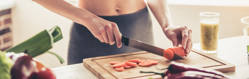 fit woman chopping vegetables, preparing a healthy meal
