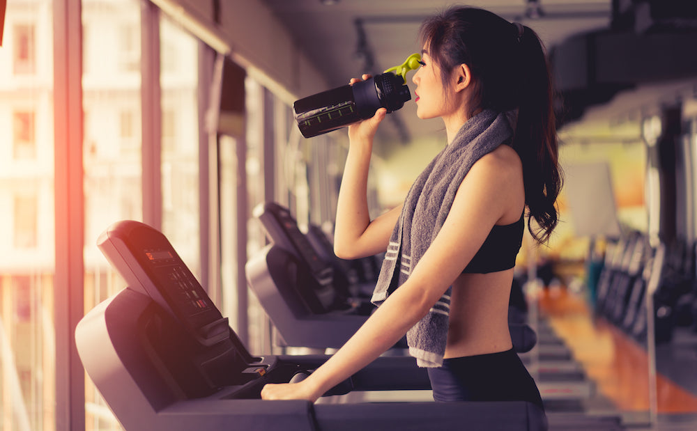 Woman drinking protein shake from bottle on treadmill