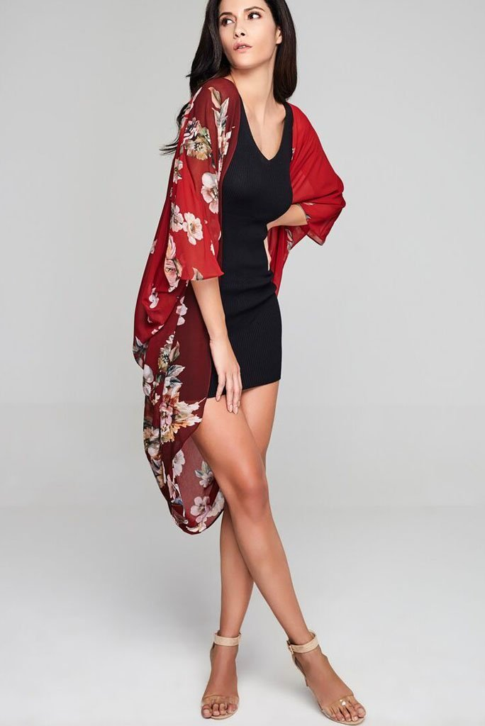 Model wearing red chiffon kimono with floral prints facing right