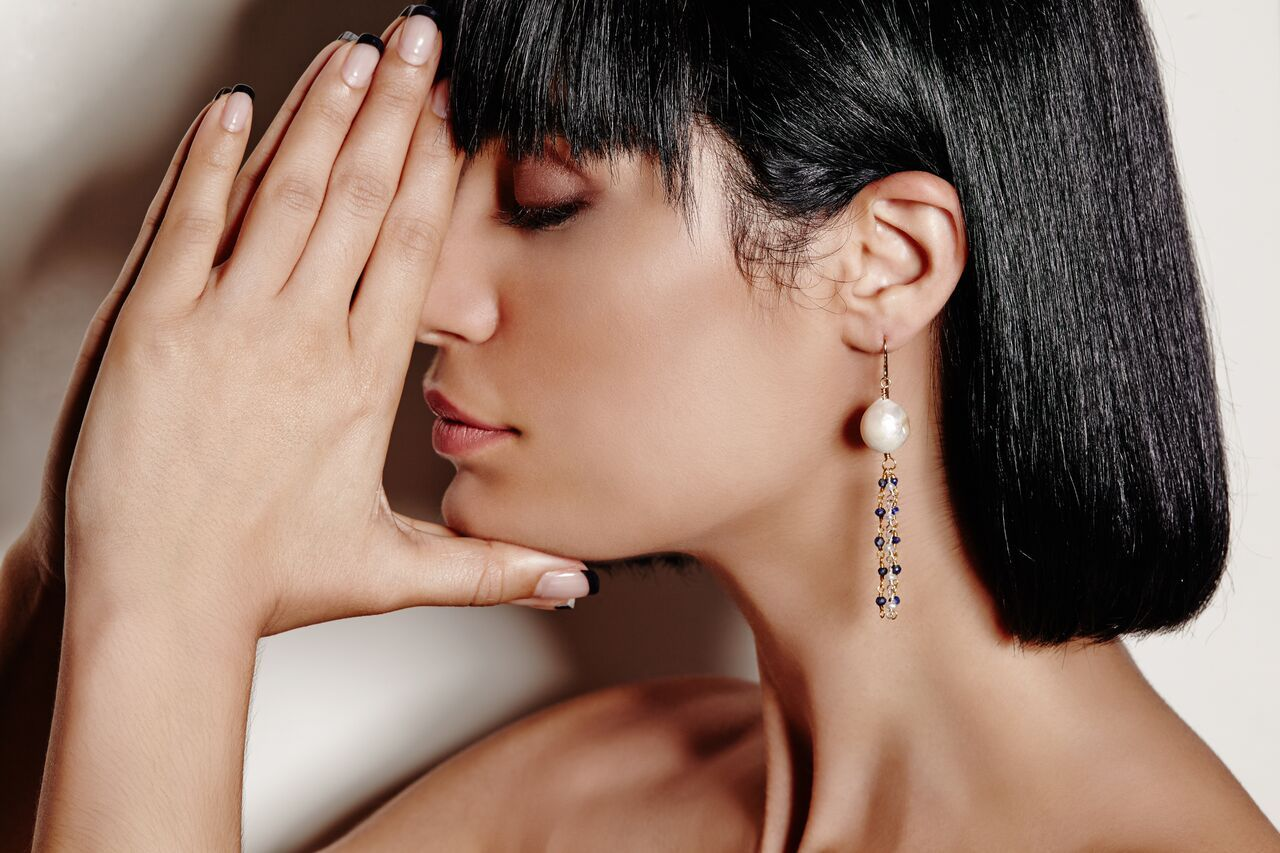 Model wearing white pearls with streaming dark cherry gemstone beads earrings