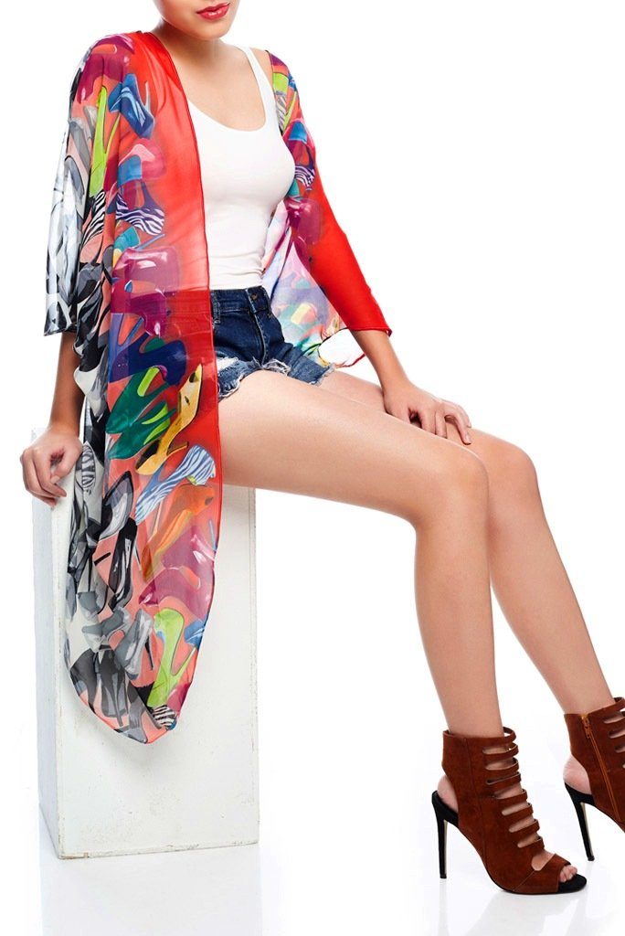 Model wearing monochrome kimono with vibrant colours seated down