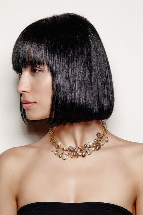 model wearing clear and umber gems among dainty gold, violet and spruce pearls necklace