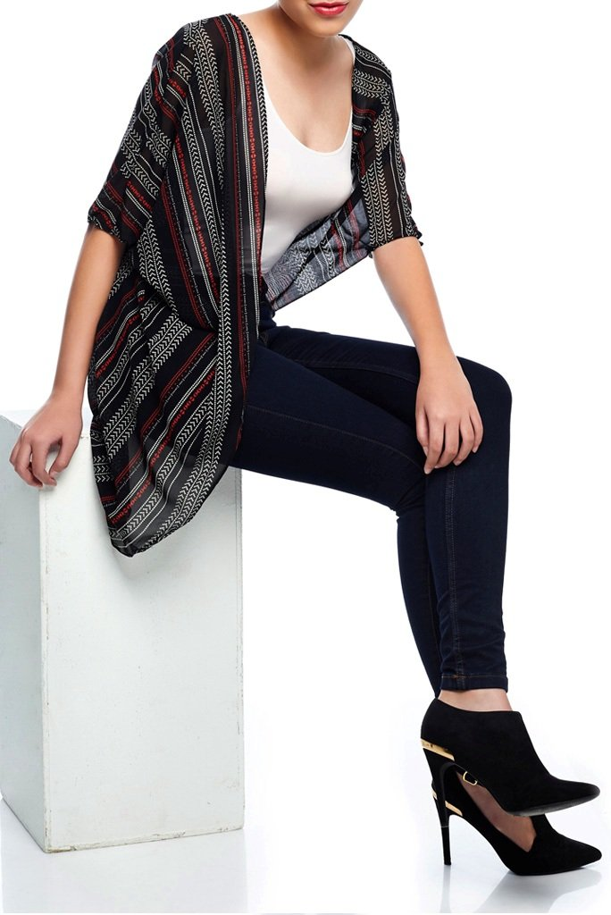 Model wearing short dark colored kimono with stripe prints seated down